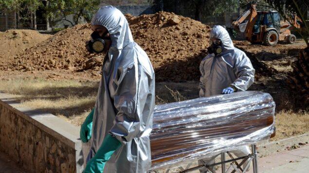 عمال ينقلون نعش ضحية كوفيد-19 ليتم دفنها في مقبرة مشتركة في المقبرة العامة في كوتشابامبا، بوليفيا، 2 يوليو 2020 (DIEGO CARTAGENA / AFP)
