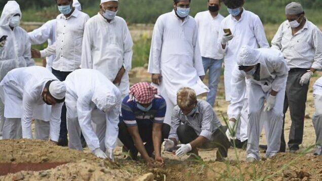 أقارب يؤدون صلاة الجنازة على شخص توفي بسبب فيروس كورونا، قبل الدفن في مقبرة في نيودلهي، 6 يوليو 2020 (Sajjad HUSSAIN / AFP)