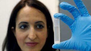 البروفسورة هداس ماماني تحمل أنبوبًا يحتوي على الإيثانول المصنوع من النفايات في مختبرها بجامعة تل أبيب، 8 يوليو 2020. (JACK GUEZ/AFP)
