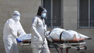 فريق طبي فلسطيني ينقل جثمان شخص توفى نتيجة مرض كوفيد-19 من المستشفى العسكري في مدينة نابلس بالضفة الغربية، 9 يوليو 2020. (JAAFAR ASHTIYEH / AFP)