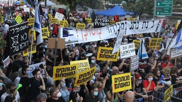 إسرائيليون يتظاهرون ضد رئيس الوزراء بنيامين نتنياهو أمام مقر الإقامة الرسمي لرئيس الوزراء في القدس، 14 يوليو، 2020. (Menahem Kahana/AFP)