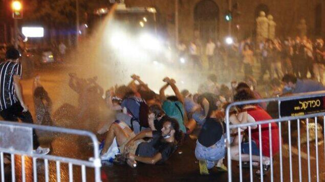 الشرطة الإسرائيلية تستخدم خراطيم المياه خلال اشتباكات مع متظاهرين ضد  ضد رئيس الوزراء بنيامين نتنياهو أمام مقر الإقامة الرسمي لرئيس الوزراء في القدس، 14 يوليو، 2020.  (MENAHEM KAHANA / AFP)