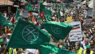أعلام الإخوان المسلمين، الأردن والأحزاب السياسية الأخرى تلوح مع لافتات احتجاجية أخرى للتنديد بالمؤتمر الاقتصادي للشرق الأوسط الذي نظمته الولايات المتحدة في البحرين، 21 يونيو 2019 (Khalil Mazraawi/AFP)