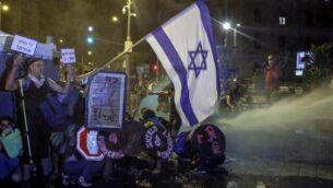 المتظاهرون يجلسون على الأرض بينما تستخدم الشرطة خراطيم المياه ضدهم في القدس، 25 يوليو 2020. (AHMAD GHARABLI / AFP)