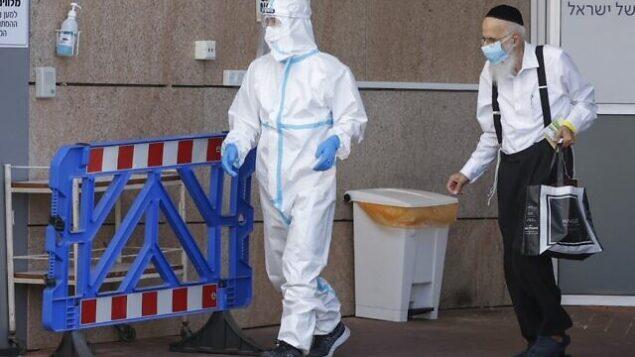 عامل طبي يرتدي زيا واقيا يرافق رجلا تم تشخيص إصابته بكوفيد-19 في المركز الطبي 'شيبا' بمدينة رمات غان، 26 يوليو، 2020.(Jack Guez/AFP)