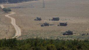 مركبات مدرعة ومدافع تنشر في الجليل الأعلى في شمال إسرائيل على الحدود مع لبنان، 27 يوليو 2020 (JALAA MAREY / AFP)
