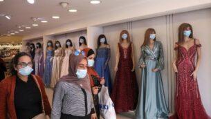 نساء فلسطينيات يرتدين أقنعة واقية وسط وباء كوفيد-19 في متجر لبيع الملابس، بينما يستعد المسلمون لعيد الأضحى في مدينة الخليل بالضفة الغربية، 27 يوليو 2020. (HAZEM BADER / AFP)