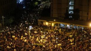 آلاف المتظاهرين يرددون شعارات ويرفعون لافتات خلال مظاهرة ضد رئيس الوزراء الإسرائيلي بنيامين نتنياهو أمام منزله في القدس، 25 يوليو، 2020.(AP/Ariel Schalit)