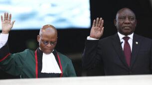 الرئيس الجنوب إفريقي سيريل رامافوسا، من اليمين، يؤدي اليمين الدستورية إلى جانب رئيس القضاة موغوينغ موغوينغ، من اليسار،  في ملعب 'لوفتوس فيرسفيلد' في بريتوريا ، جنوب أفريقيا ، السبت ، 25 مايو ، 2019. (AP Photo)