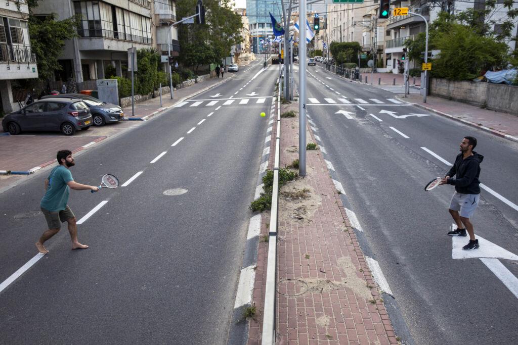 إسرائيليون يلعبون التنس على طريق فارغ أثناء الإغلاق بعد الإجراءات التي اتخذتها الحكومة للمساعدة في وقف انتشار فيروس كورونا، في رمات غان، بالقرب من تل أبيب، 9 أبريل 2020. (AP / Oded Balilty)