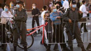 ضباط شرطة الحدود عند حاجز طريق بينما يتجمع يهود متشددون للاحتجاج على اغلاق حيهم بسبب تفشي فيروس كورونا، في القدس، 13 يوليو 2020 (AP Photo / Oded Balilty)