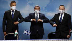 وزير الخارجية الإسرائيلي غابي أشكنازي، وسط، نظيره المجري بيتر سيارتو، يسار، ووزير العلوم والتكنولوجيا الإسرائيلي يتسهار شاي، يمين، أثناء اجتماعهم في القدس، 20 يوليو 2020. (Ronen Zvulun/Pool via AP)