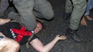 شرطي إسرائيلي يضع ركبته على متظاهر  لاعتقاله خلال ظاهرة ضد رئيس الوزراء بنيامين نتنياهو أمام منزل رئيس الوزراء في القدس، فجر الأربعاء، 22 يوليو، 2020. (AP Photo/Ariel Schalit)