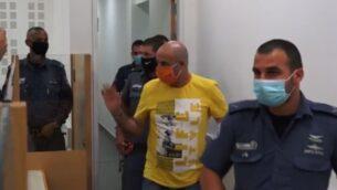 لقطة شاشة من فيديو يظهر دافيد دايم، وسط، اثناء وصوله إلى المحكمة المركزية لصدور الحكم في محاكمته بتهمة قتل زوجته السابقة، أوفيرا، 12 يوليو 2020. (Ynet)