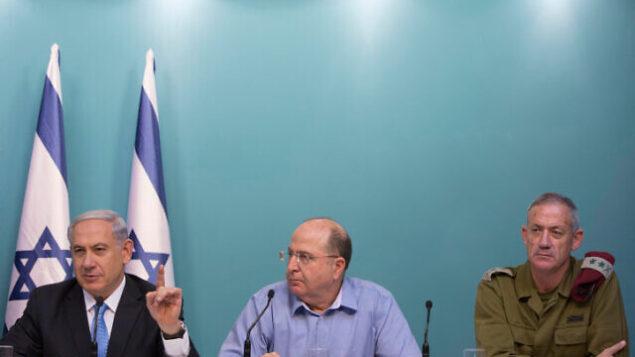 رئيس الوزراء بنيامين نتنياهو، على يسار الصورة، ووزير الدفاع آنذاك موشيه يعالون، وسط الصورة، ورئيس هيئة أركان الجيش الإسرائيلي آنذاك بيني غانتس خلال مؤتمر صحفي في القدس، 27 أغسطس، 2014.(Yonatan Sindel/Flash90)