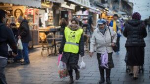 شابة تساعد سيدة مسنة في حمل أكياس البقالة في سوق محانيه يهودا في القدس، 14 فبراير، 2019.(Hadas Parush/Flash90)