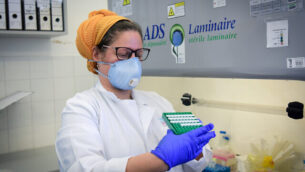 توضيحية: عاملة طبية في مستشفى 'بزيلاي' بمدينة أشكلون جنوبي إسرائيل، ترتدي معدات واقية خلال معالجتها لعينة اختبار فيروس كورونا في 29 مارس 2020.  (Flash90)