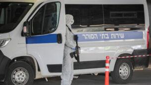 حراس سجن يرتدون ملابس واقية كإجراء وقائي ضد فيروس كورونا، اثناء نقلهم سجينًا يشتبه في إصابته بفيروس كورونا في مركز شعاريه تسيديك الطبي في القدس، 30 مارس 2020. (Yossi Zamir / Flash90)