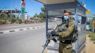 توضيحية: جندي إسرائيلي يقف عند محطة حافلات في مفرق غوش عتصيون، 28 أبريل، 2020.(Gershon Elinson/Flash90)