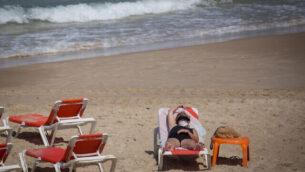 سيدة ترتدي قناعا واقيا على أحد شواطئ تل أبيب، 1 يوليو، 2020. (Miriam Alster/FLASH90)