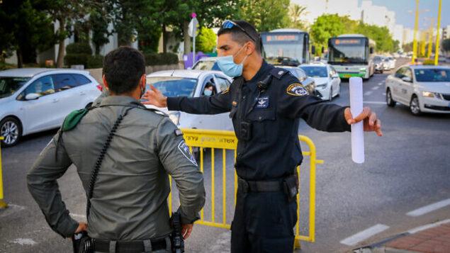 الشرطة الإسرائيلية تقف عند مدخل أحد أحياء مدينة أشدود جنوبي البلاد، 2 يوليو، 2020 خلال فرض إجراءات إغلاق على بعض الأحياء في المدينة في أعقاب انتشار فيروس كورونا. (Flash90)
