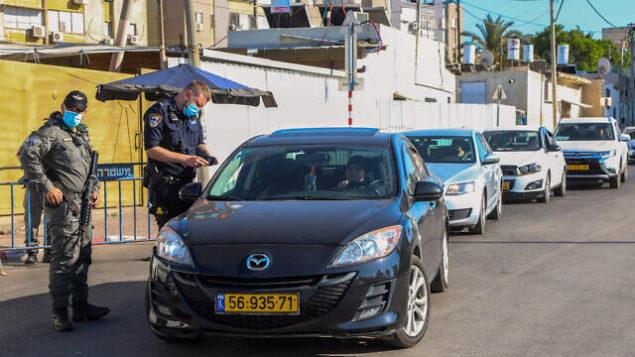 شرطيون إسرائيليون يحرسون مدخل أحد أحياء مدينة اللد، 2 يوليو، 2020، خلال إجراءات إغلاق.(Yossi Aloni/Flash90)
