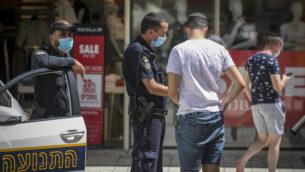 شرطي يفرض غرامة على رجل لعدم وضعه قناعا واقيا في 3 يوليو، 2020، في القدس. (Olivier Fitoussi/Flash90)