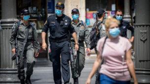 شرطيون إسرائيليون يعملون على تطبيق أنظمة الطورائ في شارع يافا بوسط مدينة القدس، 9  يوليو، 2020. (Yonatan Sindel/Flash90)