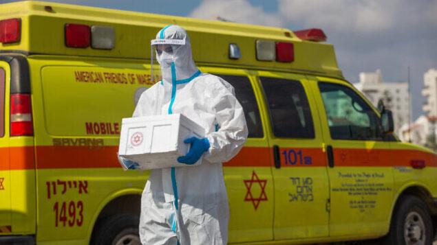 أحد العاملين في نجمة داوود الحمراء يجري فحوصات لإسرائيليين في محطة 'افحص وسافر' لجمع عينات لتشخيص فيروس كورونا في اللد، 10 يوليو، 2020. (Yossi Aloni/Flash90)