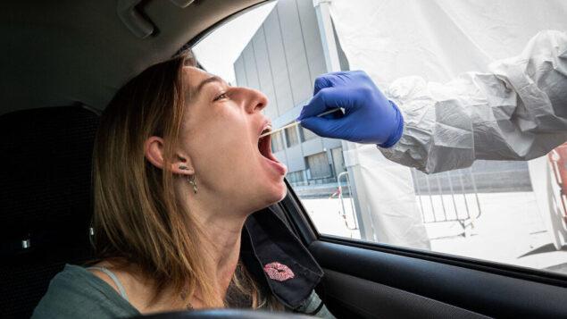 مسعف نجمة داود الحمراء يختبر امرأة في موقع اختبار لفيروس كورونا، 11 يوليو 2020. (Chen Leopold / Flash90)