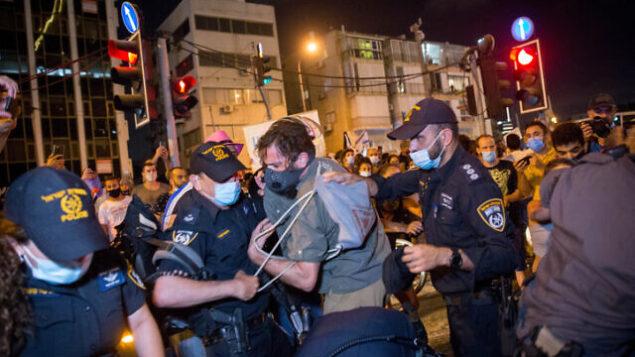 متظاهرون يتشاجرون مع الشرطة بعد مظاهرة تطالب بالحصول على دعم مالي من الحكومة وسط أزمة فيروس كورونا في تل أبيب، 11 يوليو 2020 (Miriam Alster / Flash90)