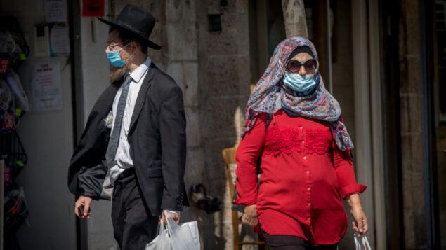 أشخاص يرتدون أقنعة الوجه بسبب تفشي فيروس كورونا في شارع يافا في وسط مدينة القدس، 13 يوليو 2020. (Yonatan Sindel / Flash90)