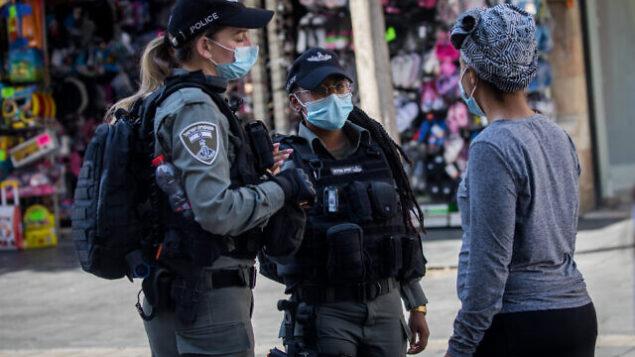 عناصر من شرطة حرس الحدود يطبقون قيود الكورونا في شارع 'يافا' بمدينة القدس، 15 يوليو، 2020.  (Yonatan Sindel/Flash90)