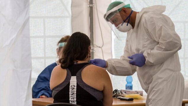 عاملون طبيون يجرون فحوصات لسكان محليين في موقع مؤقت لجمع عينات لفيروس كورونا في جنوب تل أبيب، 16 يوليو، 2020.(Flash90)