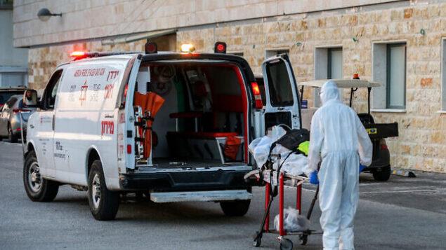 مسعف في نجمة داوود الحمراء يرتدي زيا واقيا يقوم بإخلاء مريض كوفيد-19، خارج وحدة كورونا في المركز الطبي 'زيف' بمدينة صفد، 19 يوليو، 2020.(David Cohen/Flash90)