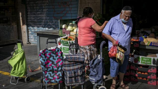 أشخاص يرتدون أقنعة الوجه بسبب تفشي فيروس كورونا ستيوقون في سوق محانيه يهودا في القدس، 21 يوليو 2020. (Olivier Fitoussi / Flash90)