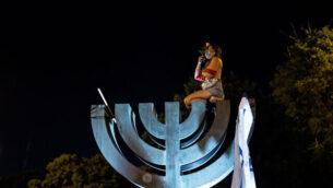 متظاهرة عارية الصدر تجلس على تمثال شمعدان بالقرب من الكنيست خلال تظاهرة ضد رئيس الوزراء بنيامين نتنياهو في القدس، 21 يوليو، 2020.(Yonatan Sindel/Flash90)