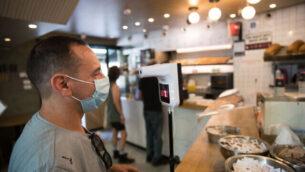 رجل يفخص درجة حرارة جسمه عند دخوله مقهى في القدس، 21 يوليو 2020 (Yonatan Sindel/Flash90)