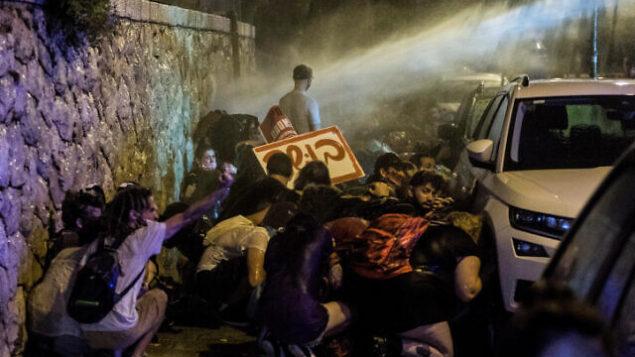 الشرطة تستخدم خراطيم المياه لتفريق المتظاهرين خلال تظاهرة ضد رئيس الوزراء بنيامين نتنياهو أمام منزله في القدس، 23 يوليو، 2020. (Noam Revkin Fenton/Flash90)