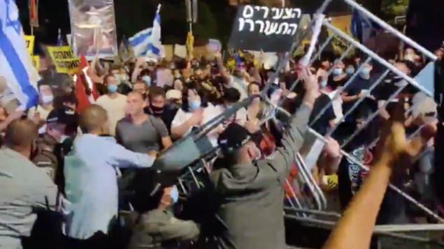 متظاهرون يحاولون إزالة حواجز خلال تظاهرة ضد رئيس الوزراء بنيامين نتنياهو  أمام مقر الإقامة الرسمي لرئيس الوزراء في القدس، 14 يوليو، 2020.  (Twitter screenshot)