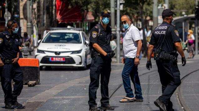 ضباط الشرطة يقومون بدورية خارج سوق محانيه يهودا في القدس لفرض قواعد الطوارئ لكوفيد-19، 3 يوليو 2020. (Yonatan Sindel / Flash90)