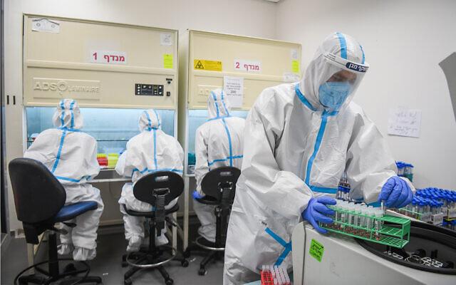 توضيحية: عمال مختبر يجرون اختبارات تشخيصية لفيروس كورونا في مختبر تابع لفرع صندوق المرضى 'مئوحيدت' في اللد، 2 يوليو، 2020. (Yossi Zeliger/Flash90)