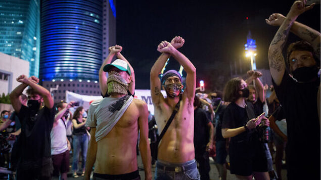 إسرائيليون من العاملين المستقلين والأحرار  يقطعون طريقًا في تل أبيب خلال احتجاج للمطالبة بدعم مالي من الحكومة، 11 يوليو 2020. (Miriam Alster / Flash90)