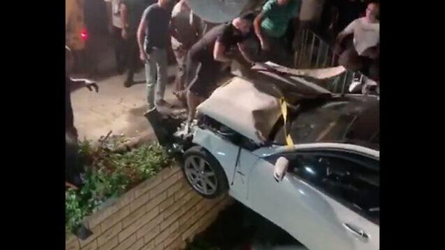 طواقم الإنقاذ ترفع مركبة من حديقة منزل في قرية عرعرة، شمال إسرائيل، 30 يوليو، 2020. (Kan screenshot)