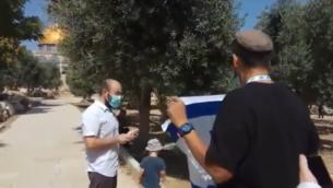 ناشط يهودي يلوح بعلم إسرائيلي في الحرم القدسي في 'تشعا بآب'، 30 يوليو 2020. (Screen capture: Twitter)