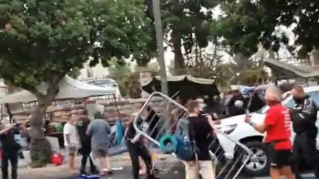 عناصر من الشرطة ومراقبو بلدية يشتبكون في متظاهرين بالقرب من مقر الإقامة الرسمي لرئيس الوزراء بنيامين نتنياهو في القدس، 13 يوليو، 2020. (Screen grab/Twitter)