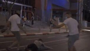 لقطة شاشة من مقطع فيديو يظهر اعتداء أشخاص يُشتبه بأنهم نشطاء يمين متطرف على متظاهرين في تل أبيب، 28 يوليو، 2020.  (Screen grab/Facebook)