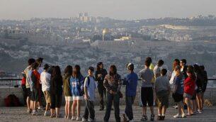 مجموعة سياح تستمع إلى مرشد سياحي في منتزه أرمون هنتسيف في القدس على خلفية البلدة القديمة في 2018. (Miriam Alster/Flash90)
