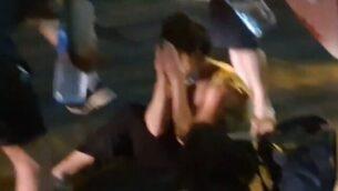 امراة تجلس في أحد شوارع تنل أبيب بعد هجوم قام به من يشتبه بأنهم نشطاء من اليمين المتطرف ضد متظاهرين شاركوا في مظاهرة ضد رئيس الوزراء بنيامين نتنياهو، 29 يوليو، 2020. (Screen grab/Ynet)