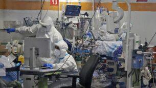مسعفون يعملون مع مرضى كوفيد-19 في جناح العزل بمركز شيبا الطبي في رمات غان، 29 يوليو 2020. (JACK GUEZ / AFP)